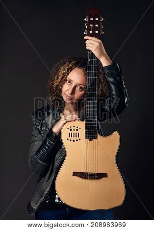Portrait of beautiful woman hugging an acoustic guitar on dark background
