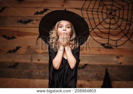 Halloween Witch concept - closeup shot of little caucasian witch child shocking face posing with bat and spider web on wooden studio background.