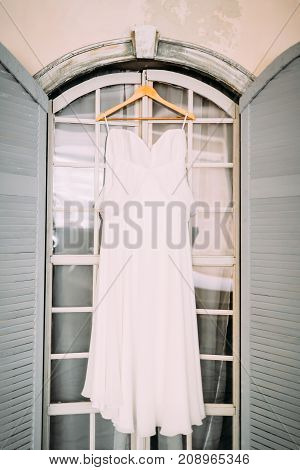A white bridal dress on wooden shoulders, against the background of a panoramic window. Artwork