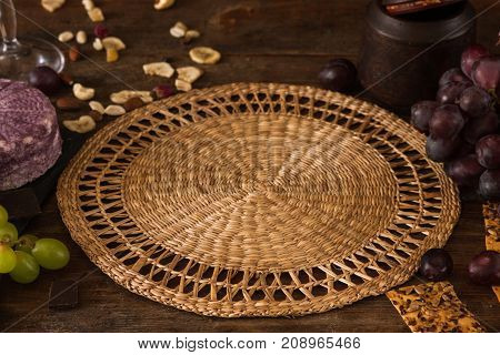 Food background of gourmet products. Void straw mat with quality sort of cheese and assortment of appetizers, close up