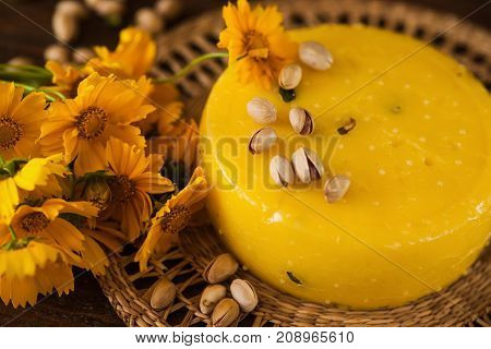 Food composition of gourmet cheese, close up top view. Quality sort of Caciotta with pistachio and flowers, sunny mood concept. Dairy local industry