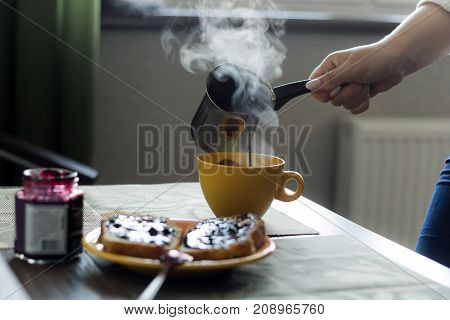 Woman Pours Hot Coffee From Cezve In  Mug In Front Of The Window