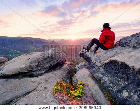 Hiker man take a rest on mountain peak. Man lay on summit bellow autumn valley. Bright morning Sun shining in sky.