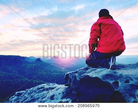 Alone Tourist With Cap And Sporty Outdoor Clothes Stand On Cliff Edge Watching Into National Park Va