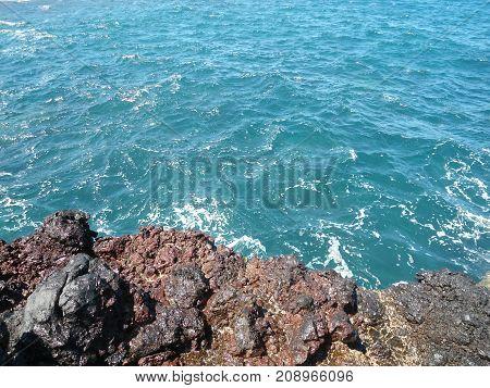 Hardened volcanic lava in blue Indian ocean