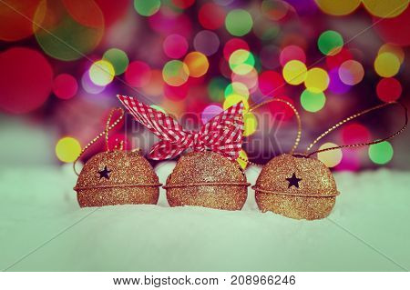 Greeting Christmas Card with Gold Jingle Bells on Colorful Bokeh Background. Toning image