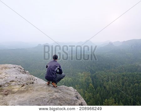 Rear View Of Alone Hiker In Dark Outdoor Suit Sit On The Edge. Sharp Rocky Peak  Above Mountains Val