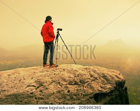 Art Photographer On Location Takes Photos With Camera On Peak Of Rock. Foggy Landscape