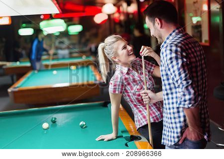 Young couple enjoying playing snooker on date together