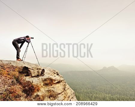 Hiker With Camera On Tripod Takes Picture From Rocky Summit. Alone Photographer  On Summit