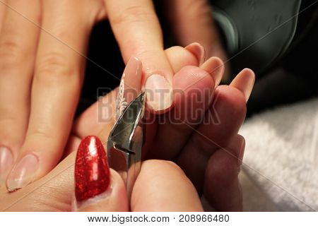 manicurist at training courses shows students how to handle nails with the help of nippers cuticles before applying shellac