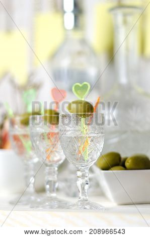Vodka in the glass with olive. Drink bar party.