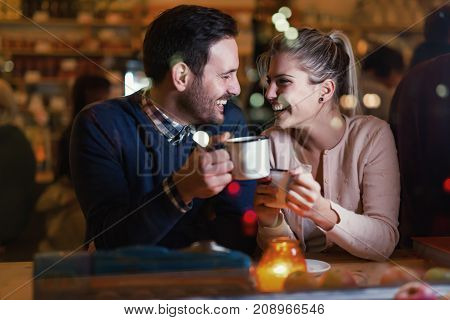 Happy attractive couple talking at bar having date
