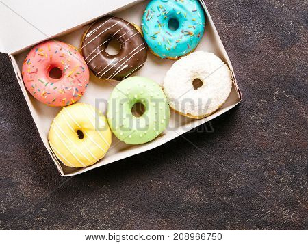 Top view of paper box with colorful donuts on dark cement background. Copy space.
