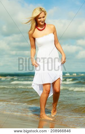 Attractive blonde woman wearing long white romantic dress walking in water sea during summer.