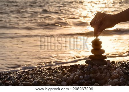 Female hand setting a pebble to the top of the pyramid against the background of the evening sea. Seascape. The concept of balance and spirituality.