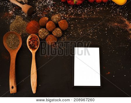 Spicy cheese assortment. Healthy rustic food with free space. Gourmet sorts of dairy with spices on black background, recipe and menu concept