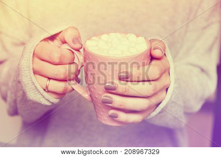 female hands holding pink cup of coffee with marshmallow