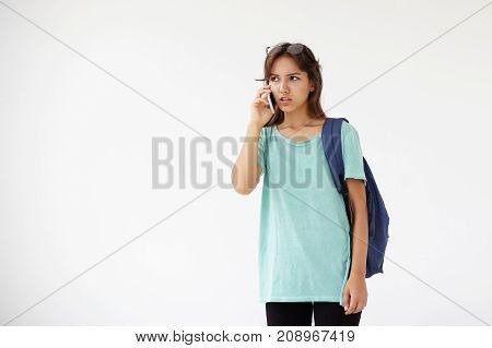 Youth learning education modern technology and communication concept. Portrait of frustrated Latin college girl with backpack talking on smart phone frowning having argument expressing dissent
