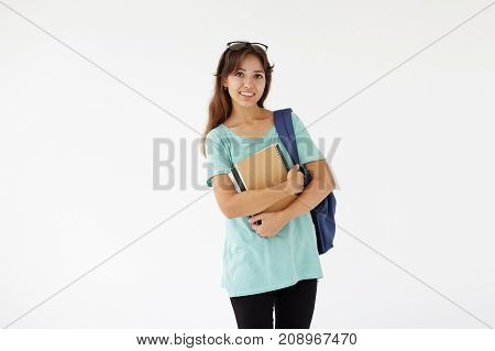 Isolated shot of cute casually dressed female A-student of mixed race appearance carrying backpack on her shoulder and holding books going to classroom looking at camera with happy confident smile