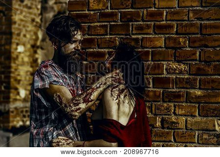 Halloween zombie couple standing on brick wall. Woman with red blood and brunette hair. Bearded man or war soldier with wounds. Holiday celebration concept. Girl vampire in torn clothes.