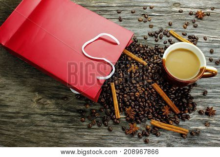 Coffee beans anise and cinnamon were scattered from the red packing on a wooden table. A cup of coffee on a wooden table View from above