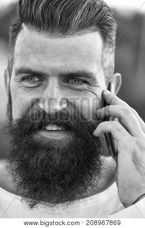 Closeup portrait view of one handsome young smiling man with long dark haired beard speaking on mobile phone outdoor on blurred green natural background Vertical picture