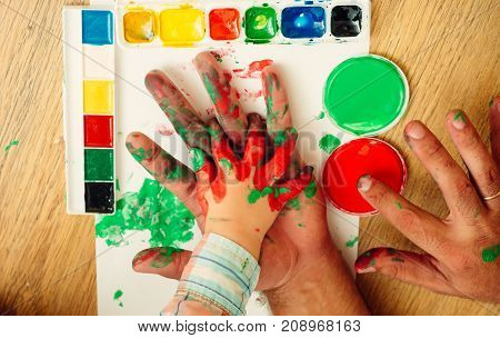 Hands drawing with paints and multicolor palette on white paper. Arts and crafts. Handprint painting concept. Fathers day family love and care. Imagination creativity and freedom.