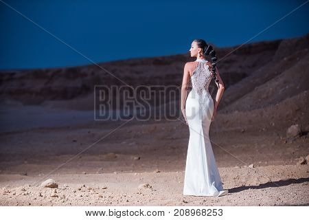 Bride in sand dunes on mountain landscape. Honeymoon travel concept. Summer vacation and holidays. Woman in white wedding dress in desert. Girl posing on evening sky back view