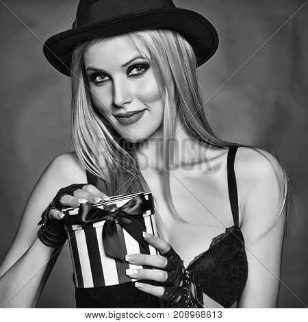 One attractive sexual happy smiling young blonde woman with long hair in red hat gloves and bra holding roung present box for christmas valentine or new year on pink backdrop square picture