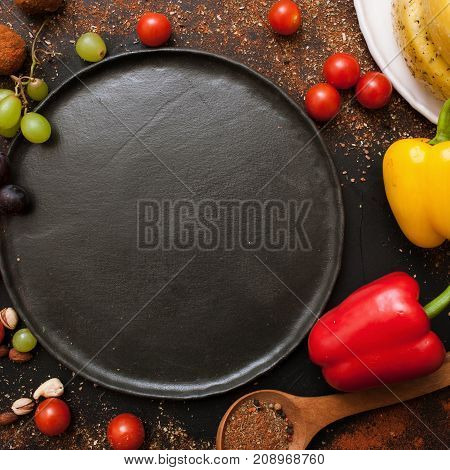 Healthy food and empty plate top view. Close up background of vegetables and spices, free space black dish. Recipe, cuisine and menu concept
