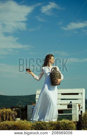 Summer vacation holidays and celebration. Model with alcohol drink on sunny day. Woman with glass of red wine and wicker bottle. Winery tour concept. Girl in white dress posing on blue sky.