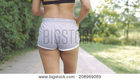 Crop back view of woman wearing gray sportive shorts and running down road in summer green park working out alone.