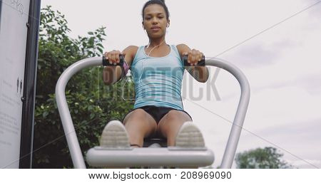 From below shot of ethnic sportive woman with headphones training back muscles while sitting on exercise equipment and looking at camera at street.