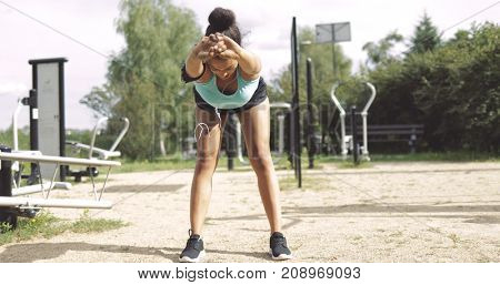 Anonymous ethnic woman in sportswear bending forward and stretching body while standing on sports ground in summer park.