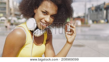Portrait of young woman in yellow tank top wearing white headphones on neck and looking at camera on urban background.