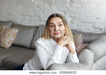 People lifestyle leisure time rest and relaxation concept. Confident 50 year old mature woman wearing her long hair loose resting on couch in modern home interior clasping hands in front of her