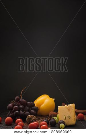 Gourmet sorts of cheese with variety of vegetables, fruits and spices on black background. Still-life composition of luxury products, close up, free space.