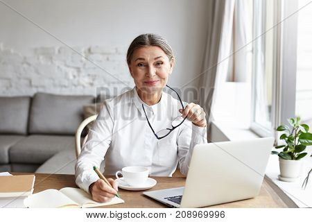 Cheerful skilled middle aged life or business coach enjoying creative process of making new text sitting at her workspace writing down thoughts ideas in copybook with mug books and laptop on desk