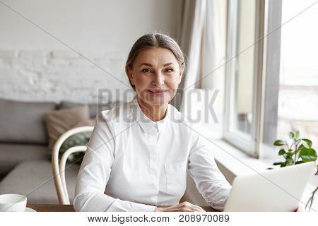 Portrait of happy skilled middle aged woman life coach business consultant psychologist or medical advisor smiling joyfully at camera working on laptop enjoying her job helping people online