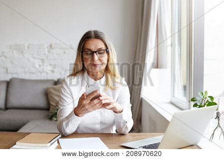Confident successful middle aged woman chief editor of large publishing company sitting at her spacious modern office with books and laptop pc on desk dialing phone number of prospective young writer