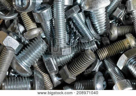 A bunch of large and small bolts with different heads. New and old bolts mixed up. Washers and nuts serrated and flat. Heads various hexagonal semicircular hexagon.