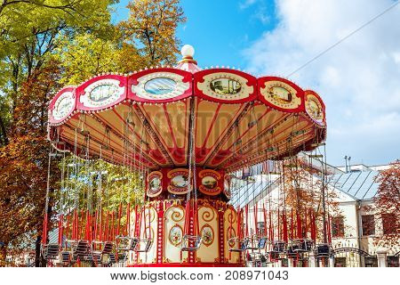 Empty Carousel Merry-Go-Round With Seats Suspended On Chains Without People Waiting For Its Visitors.  Attractions in the autumn, closing of attractions