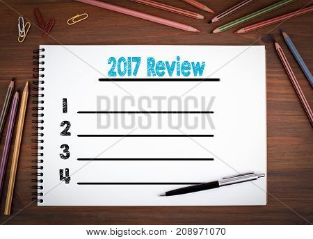 2017 review blank list. Notebooks, pen and colored pencils on a wooden table..