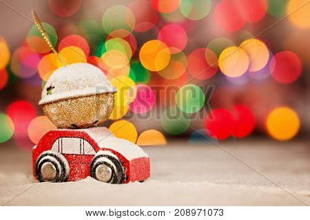 Miniature Red Car Carrying a Gift in a snowy landscape. Holiday Merry Christmas concept.
