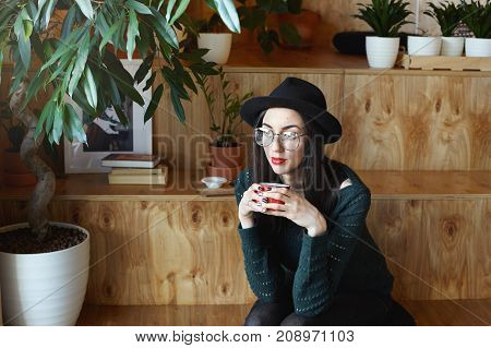Portrait of stylish hipster girl wearing red lipstick round eyeglasses and black hat relaxing at coffee house with cozy interior holding mug in hands enjoying hot chocolate having thoughtful look