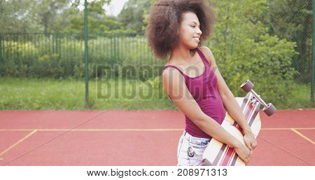 Beautiful and confident woman in stylish summer outfit holding skateboard and posing coquettishly on sports ground.