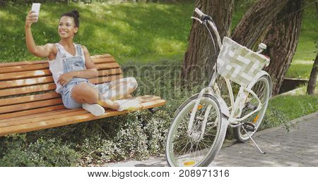 Young woman sitting on wooden bench in summer park with white bicycle parked near and smiling while posing for selfie.