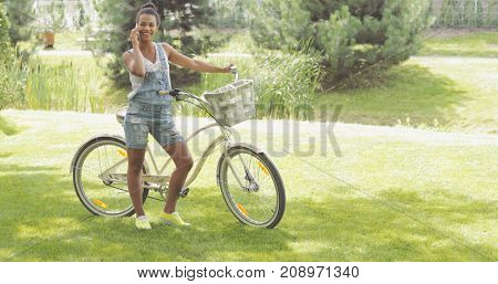 Confident young girl in casual clothing posing in park standing with bicycle and talking phone while smiling away.