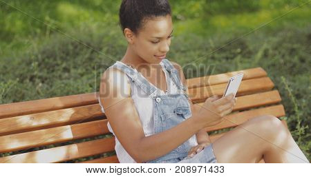 Content young ethnic girl in denim overall and tank top sitting on wooden bench in park and taking selfie looking at smartphone.